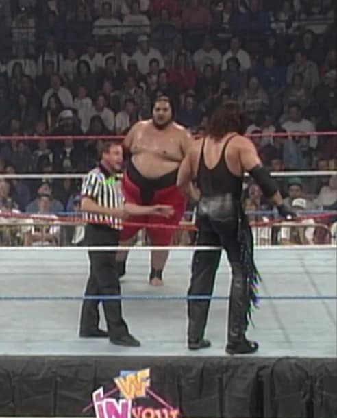Yokozuna in the ring with a referee and Undertaker