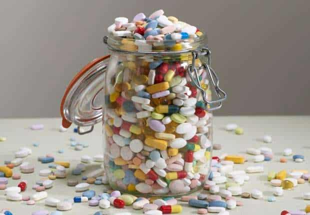 a jar of multicolored pills overflowing onto a table