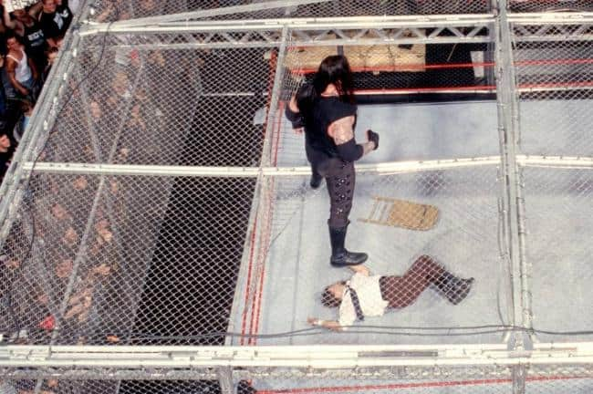The Undertaker gazes down at the limp body of Mick Foley after taking his now infamous fall through the Hell in a Cell cage