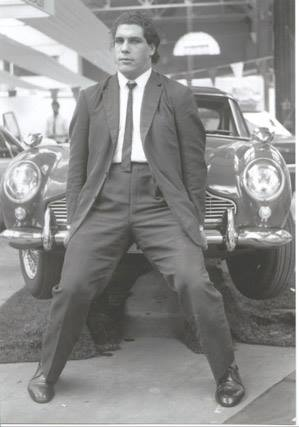 Andre the Giant in a suit picking up the front of a car when he was younger