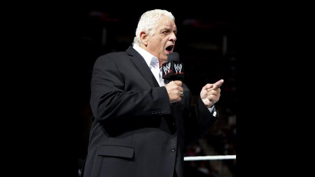 Dusty while working for the WWE in a black suit talking on a microphone