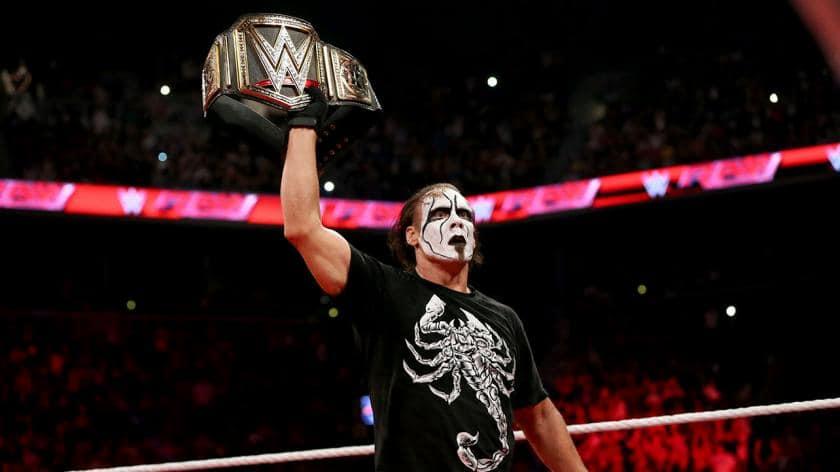 sting holding up the WWE World Heavyweight Title Belt