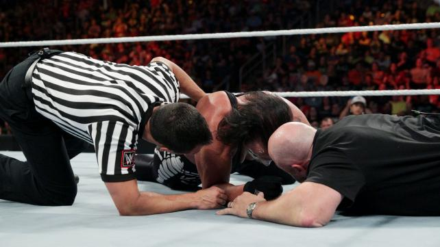 The doctor and referee on the mat checking on Sting in WWE