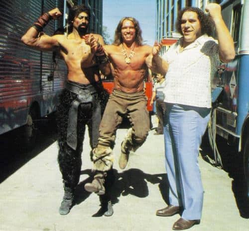NBA basketball great Wilt Chamberlain and Andre the giant holding up Arnold Schwarzenegger in the air to show their strength on the set of Conan The Destroyer