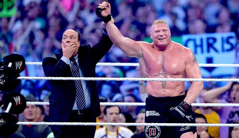 Brock Lesnar and Paul Heyman with hands up in victory after a match