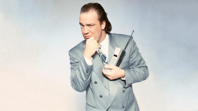 Paul Heyman in a grey suit holding a early 1980's cell phone with his hand up to his chin