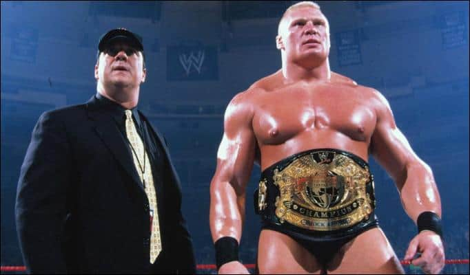 Paul Heyman in a black suit and baseball cap standing next to Brock Lesnar wearing a title belt