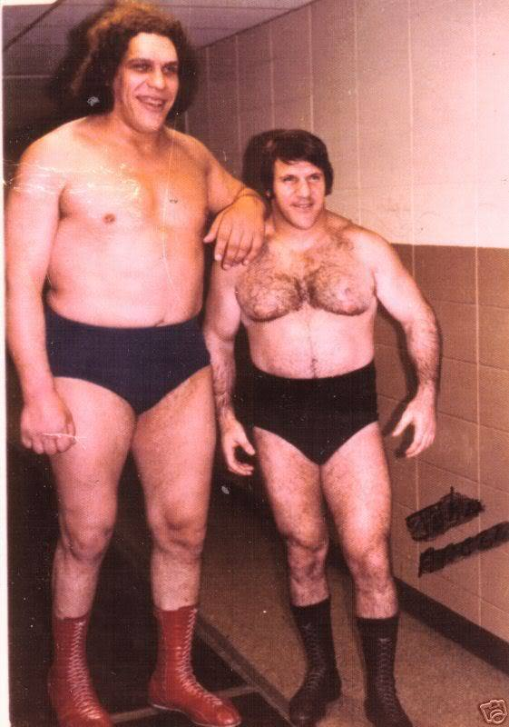 Andre the Giant with his arm on the shoulder of Bruno Sammartino in their wresting trunks next to a concrete wall