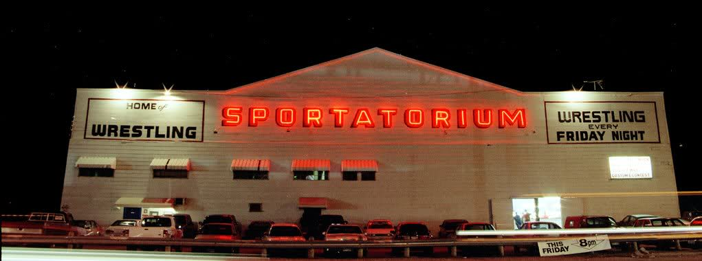 Iconic Dallas Sportatorium at night with the name lit up in red.