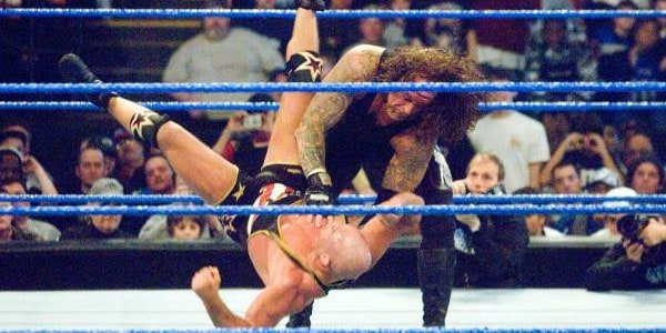 In the ring The Undertaker chokes out Kurt Angle