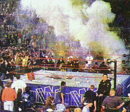 photo of the aftermath from the WWE Riot that ensued at a WWF house there's smoke, garbage and chairs all over the ring