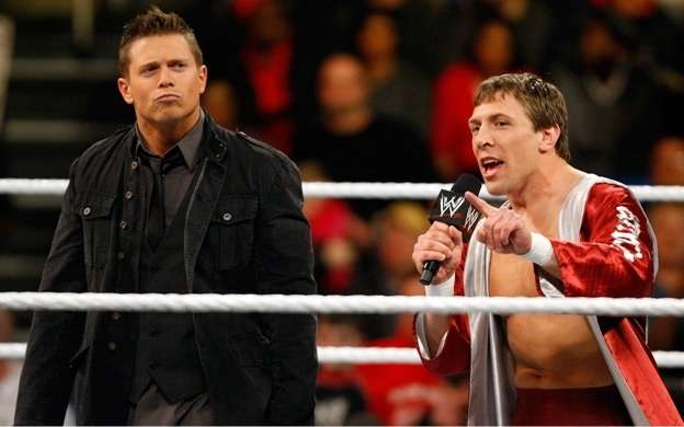 the miz in all black clothes and daniel bryan on the WWE microphone in the ring talking smack