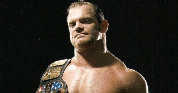 Chris Benoit posing with his title belt on his shoulder