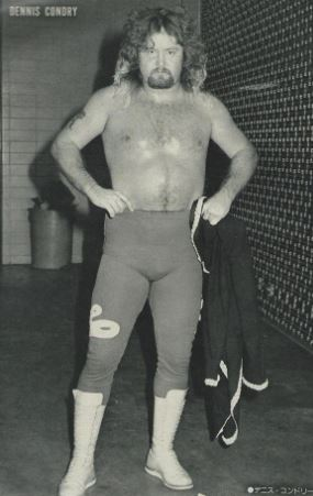 """""""Loverboy"""" Dennis Condrey in wrestling tights and hands on his hips before a match"""