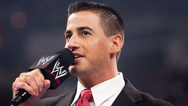 Justin Roberts in a dark suit with read tie on the WWE Microphone