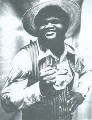 Norvell Austin, founding member of The Midnight Express, in a straw hat, striped vest and satin shirt holding glasses
