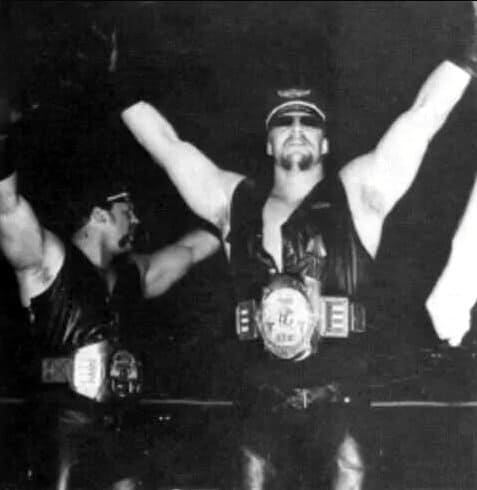 The Road Warriors in all black leather in the ring with title belts on and arms in the air working the crowd