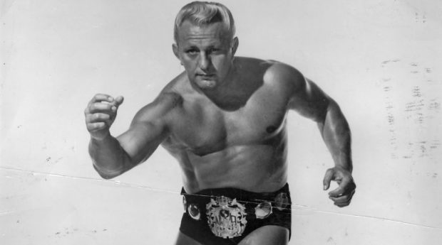 Buddy Rogers posing in his title belt as the NWA world heavyweight champion.