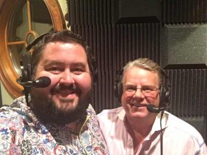 Conrad Thompson and Bruce Prichard working on the podcast with headsets on