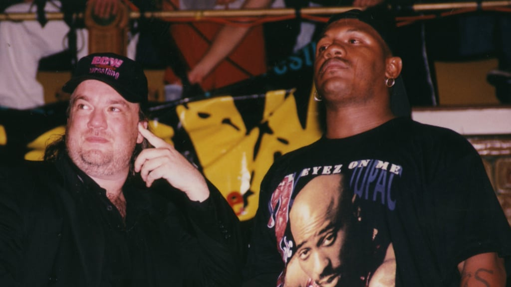 Paul Heyman and New Jack in casual clothes standing beside a ring