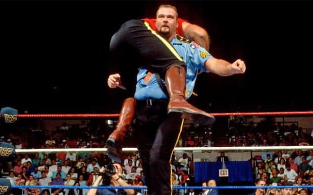 Big Boss Man, Ray Traylor, in his signature corrections officer uniform, with a wrestler hoisted over his shoulder