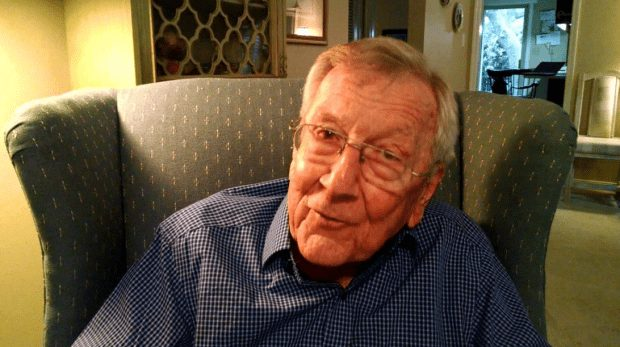 Lance Russell in his golden years sitting in an arm chair smiling