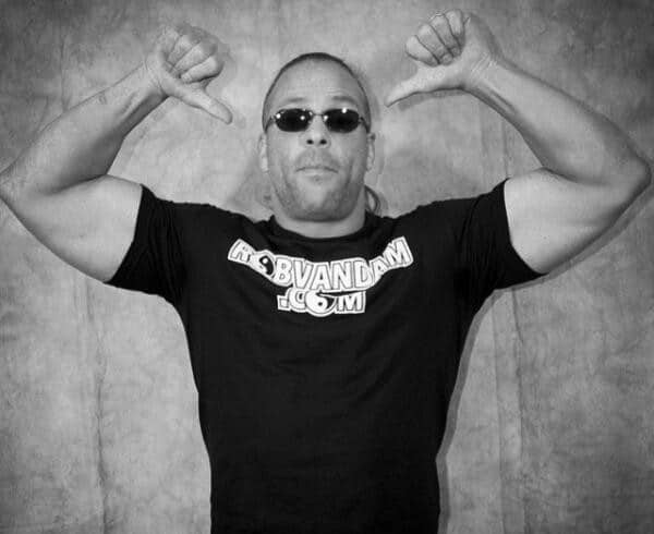 Rob Van Dam in a Robvandam.com Tshirt showing off his muscles with thumbs pointing to himself
