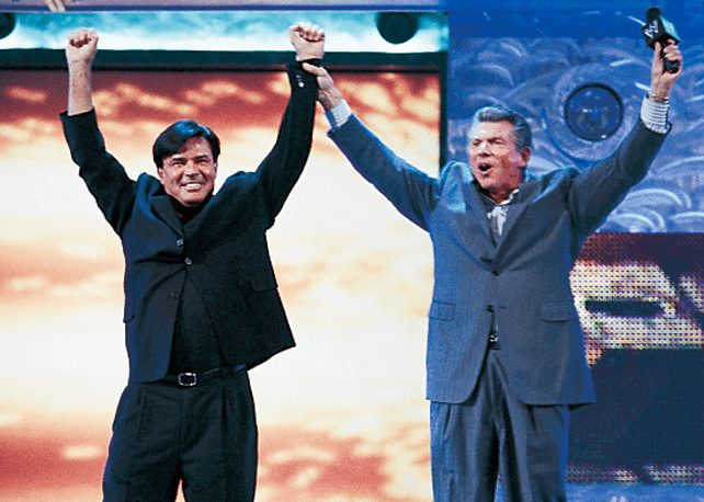 Vince McMahon and Eric Bischoff in WWE Return joining hands raised in the air