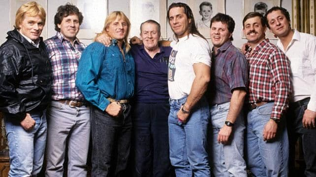Stu Hart of the Hart Wrestling Family posing with sons Bret and Owen at his sides along with other members of the Hart Wrestling Family