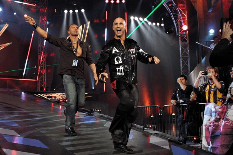 """Frankie Kazarian and Christopher Daniels as part of Bad Influence enter on a stage to wrestling music """"Devious"""" to laser lights"""