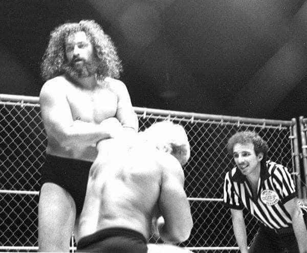The steel cage match with Bruiser Brody putting Lex Lugar on his knees with referee Bill Alfonso, War Memorial Auditorium, Florida, January 1987