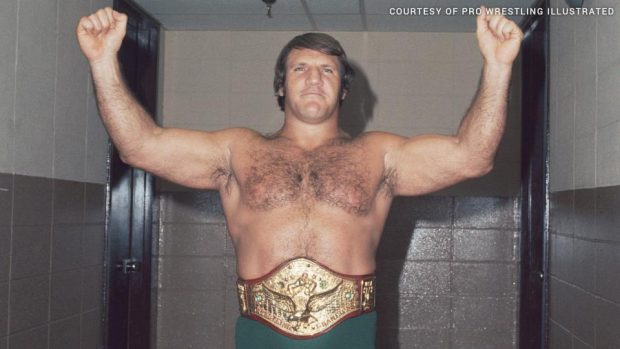 Bruno Sammartino in his title belt showing off as victor with arms in the air doing a strong man pose