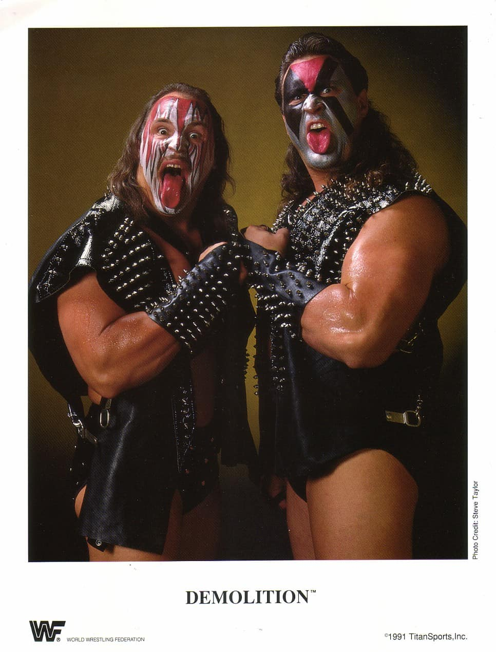 Tag Team Demolition (Crush and Smash version) in black leather studded vests, red black and silver makeup on their face and their tongues hanging out