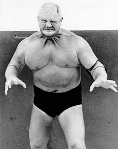 'The World's Most Dangerous Wrestler,' Dick the Bruiser with his neck muscles strained from a mean face in his wrestling trunks