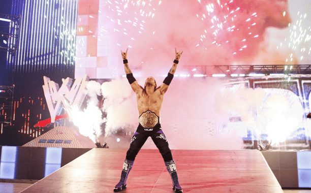 """Edge entering an arena to wresting music """"Metalingus"""" with pyrotechnics going off in the background he's in a title belt with his hands up in the air giving the rock on hand signal"""