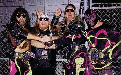 Wrestling Tag Team The Fabulous Freebirds (Fantasia / Badstreet version) in pink green and black wrestling tights piling their hands on top of each other in front of a barbwire fence