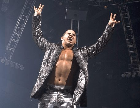 """Matt Hardy in a silver satin suit and not shirt with arms in the air entering to wrestling music, """"Live for the Moment"""""""