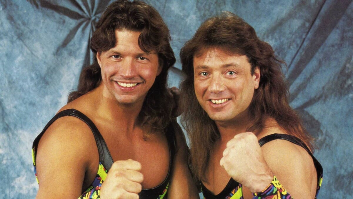 Tag Team The 'New' Rockers Posing in singlets with their fists up to show their strength