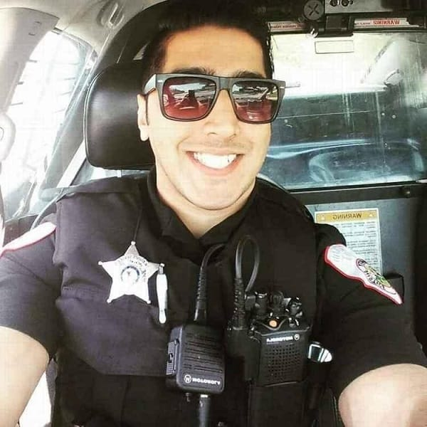 Mustafa Ali in his police uniform taking a selfie inside the police car