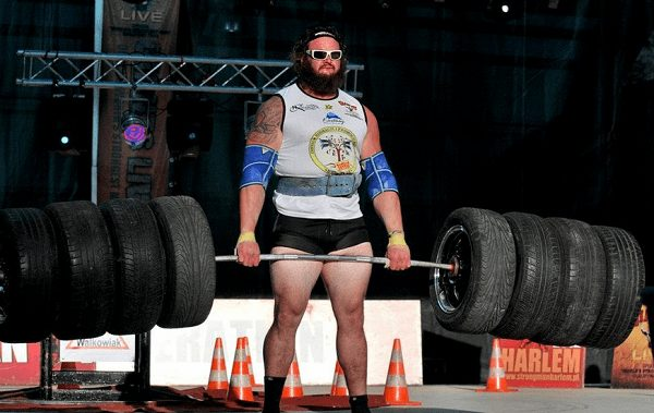 Wrestlers Outside the Ring Braun Strowman's as a Strongman holding 8 weighted tires on a barbell