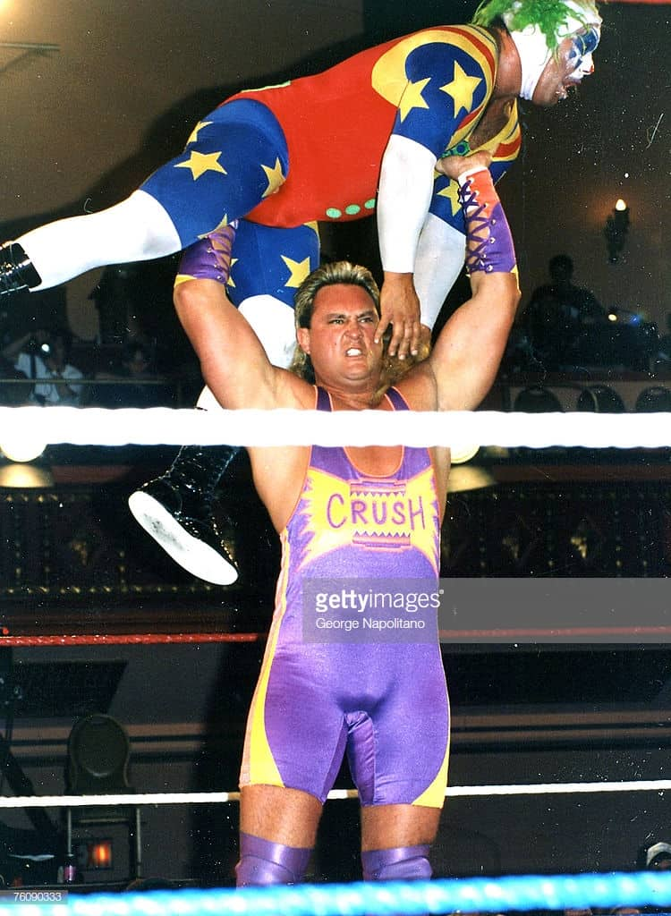Wrestler Brian Adams holding Doink the Clown Matt Borne above his head