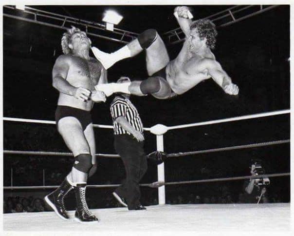 Black and white photo of Curt Hennig hitting a dropkick on Nick Bockwinkel in AWA