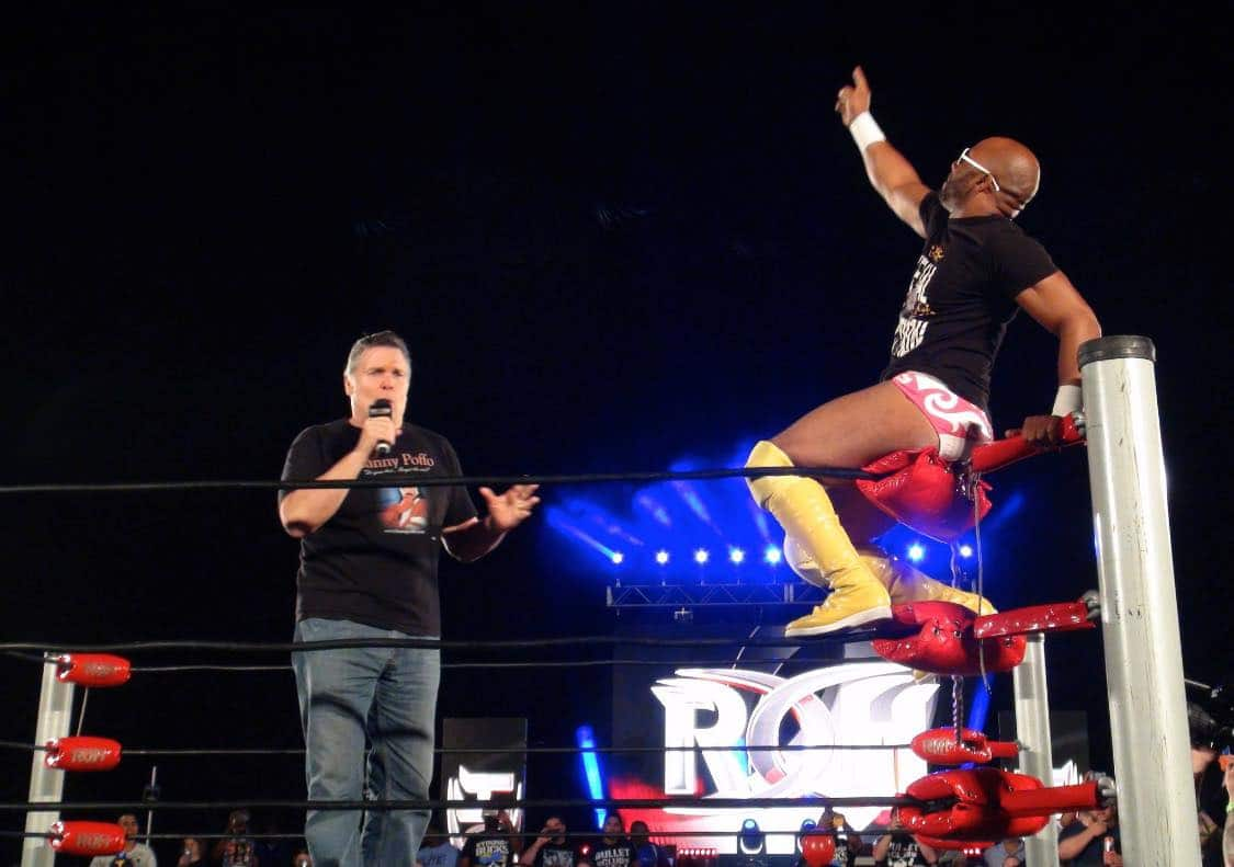 Lanny Poffo talking into the microphone wearing a black t-shirt an jeans with Jay Lethal sitting on the top turnbuckle with sunglasses on and pointing to the sky in honor or Randy Savage at an April 2018 Ring of Honor show