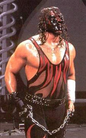 Kane at Judgment Day 2001, wearing a black vested one piece with red flames, noticeably exposing parts of his body once presumed burned.