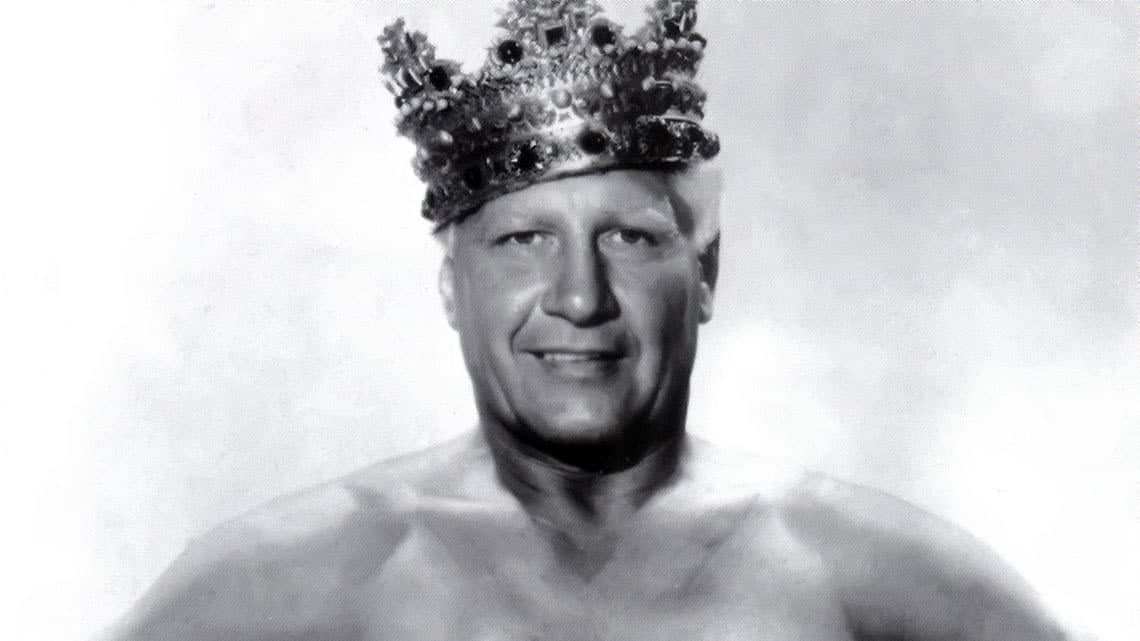 Black and white photo of a shirtless 'Classy' Freddie Blassie with a crown on his head