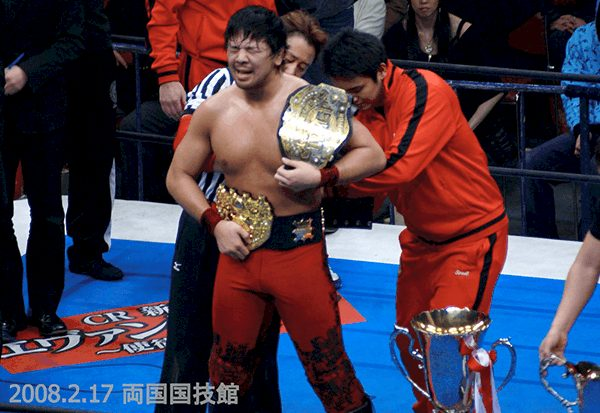 YoungLion, Kazuchica Okada, helps Shinsuke Nakamura with his belts