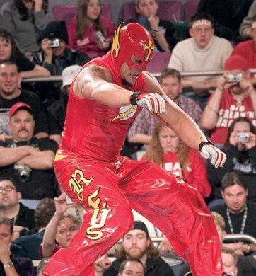 Rey Mysterio as The Flash. Rey wore red trousers and a vest, although the shade were slightly brighter and more in tune with that of the Scarlett Speedster. His side