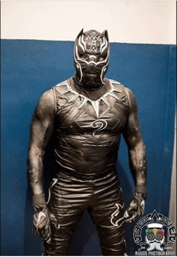 Rey Mysterio and his portrayal of the King Of Wakanda, The Black Panther. Rey donned the suit back in November 2017 in a four-way match against La Mascara, Rush and Penta Zero M.  The suit included T'chilla's silver iconic necklace and the masked wings curled up into feline ears.