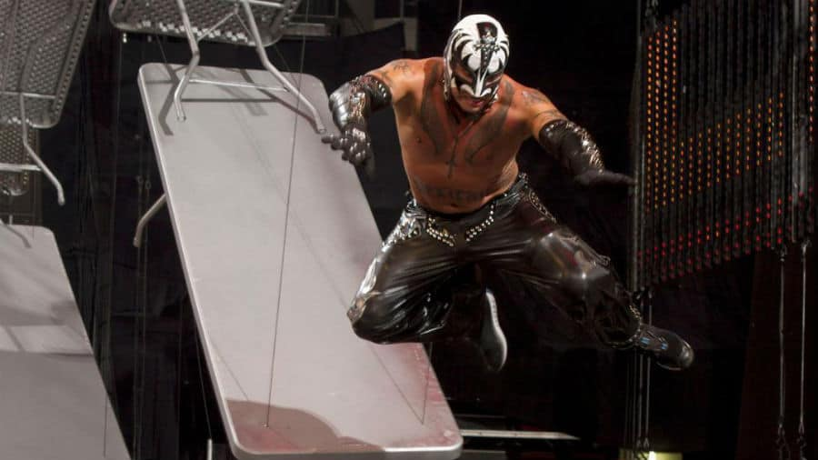 Rey Mysterio must be a fan of glam rock icons Kiss as he has worn the face-painted band's colors on quite a few occasions, most notably at WWE's TLC 2010. Rey's black tights, gloves and gauntlets are studded with rhinestones and his white mask is accentuated with black markings of bassist Gene Simmons Demon makeup.