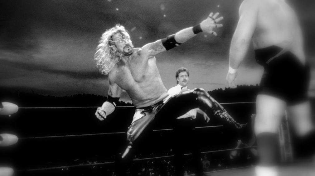 A black and white photo of Diamond Dallas Page about to strike in the ring at an outdoor WCW event in 1997
